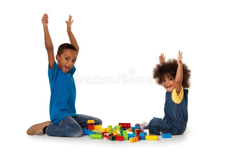 Petits enfants enthousiastes africains jouant avec un bon nombre de blocs en plastique colorés d'intérieur photographie stock