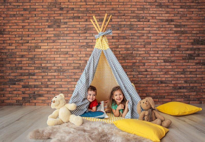 Petits enfants espiègles dans la tente faite main photos stock