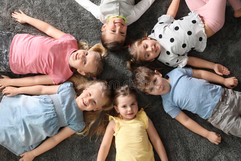 Petits enfants espiègles se trouvant sur le tapis à l'intérieur images libres de droits