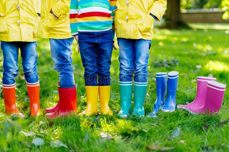 Petits enfants, garçons ou filles dans les jeans et la guêpe dans des bottes de pluie colorées image stock