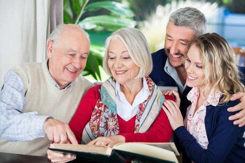 Petits-enfants heureux avec le livre de lecture de grands-parents image libre de droits
