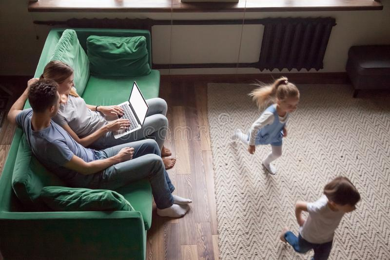 Petits enfants jouant le rattrapage tandis que parents à l'aide de l'ordinateur portable photographie stock