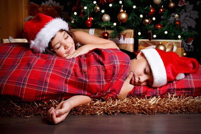 Petits enfants mignons attendant des cadeaux de Noël photos libres de droits