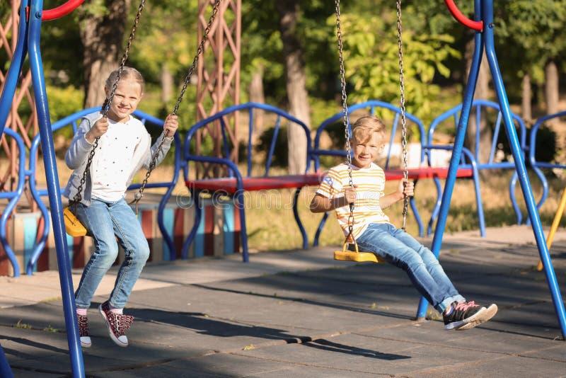 Petits enfants mignons jouant sur des oscillations dehors images stock