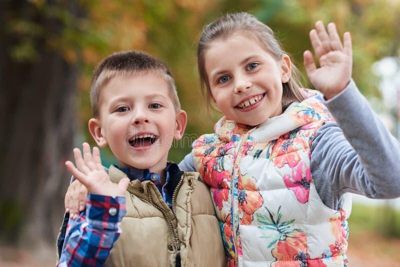 Petits enfants mignons ondulant le bonjour en parc photos libres de droits