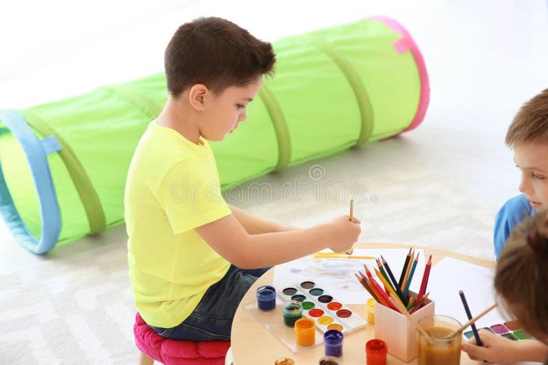 Petits enfants mignons peignant à la table dans la chambre image libre de droits