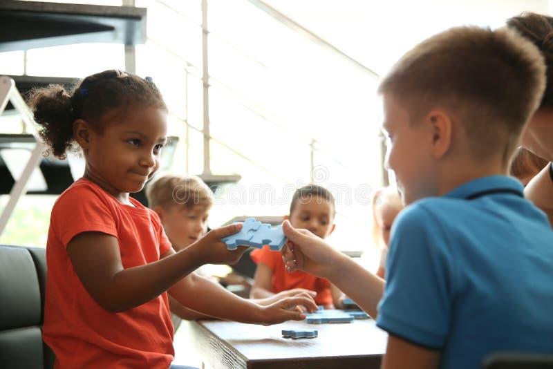 Petits enfants tenant des morceaux de puzzle dans des mains images libres de droits