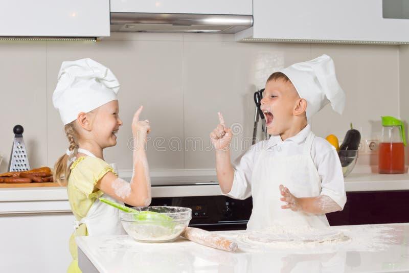 Petits enfants très heureux dans le vêtement de chefs images stock