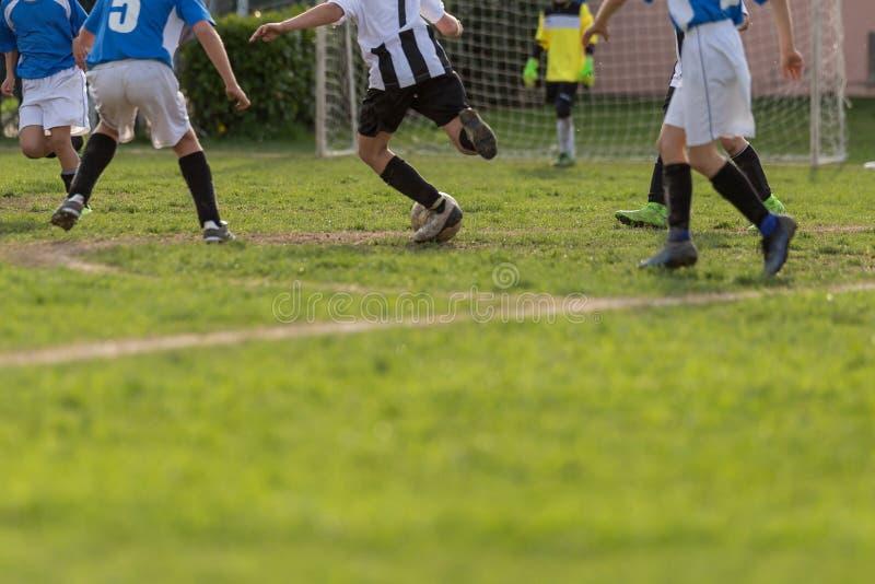 Petits footballeurs pendant le match : Plan rapproché de Children& x27 ; jambes de s photos libres de droits