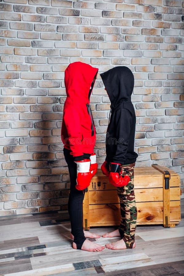 Petits frères jumeaux s'habillant dans les gants de boxe de port de vêtements de sport posant dans un studio photo stock