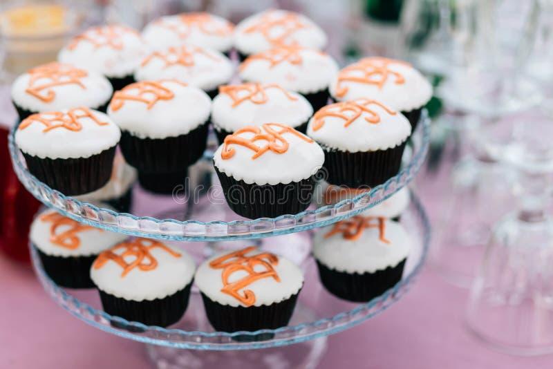Petits gâteaux avec des initiales des jeunes mariés sur un support à deux niveaux à un mariage photos stock