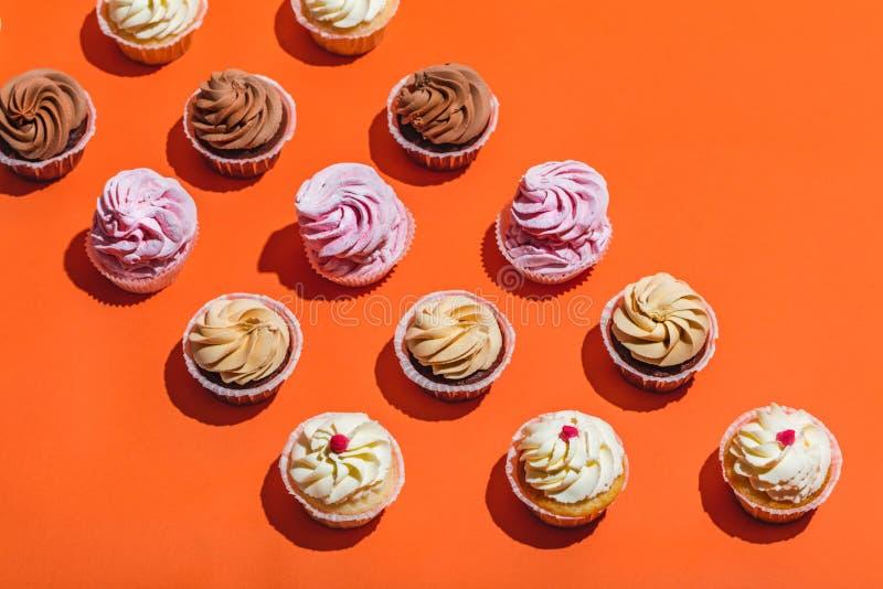 Petits gâteaux colorés dans trois rangées sur le fond orange photographie stock