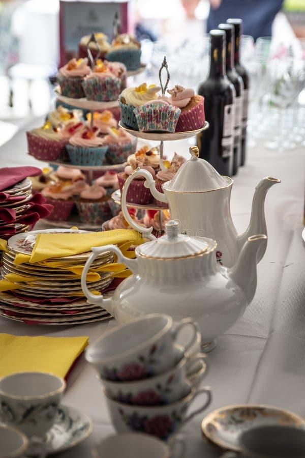 Petits gâteaux décorés sur le plateau et la table de gâteau image stock
