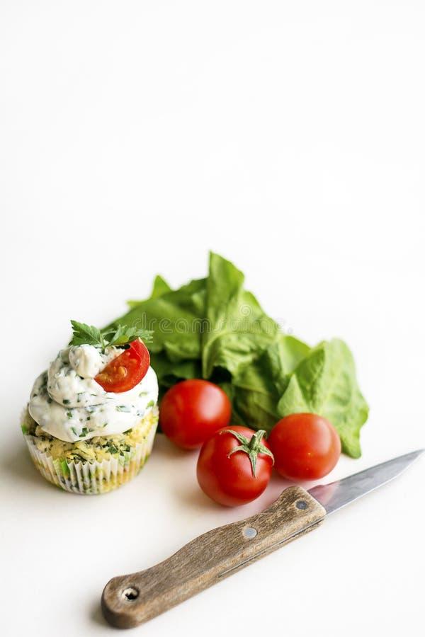 Petits gâteaux d'épinards avec le givrage de crème de fromage, oignon frais vert sur un fond blanc avec des tomates-cerises et de photo stock