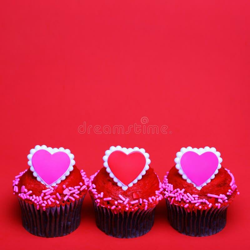 Petits gâteaux de chocolat avec des coeurs de Valentine sur les dessus, au-dessus du rouge photographie stock libre de droits