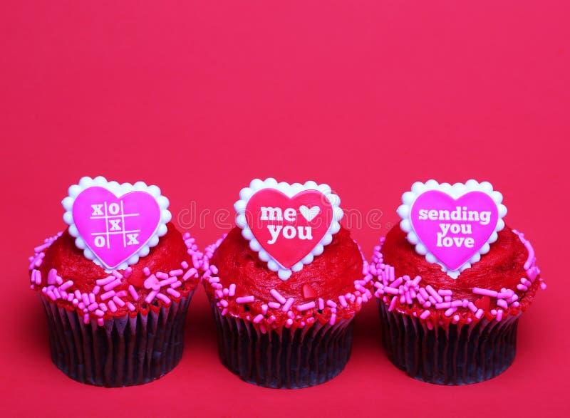 Petits gâteaux de chocolat avec des coeurs de Valentine sur les dessus, au-dessus du rouge photos libres de droits