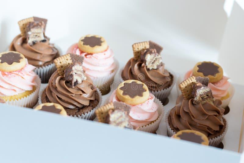 Petits gâteaux de chocolat et de vanille dans un boîtier blanc photo stock
