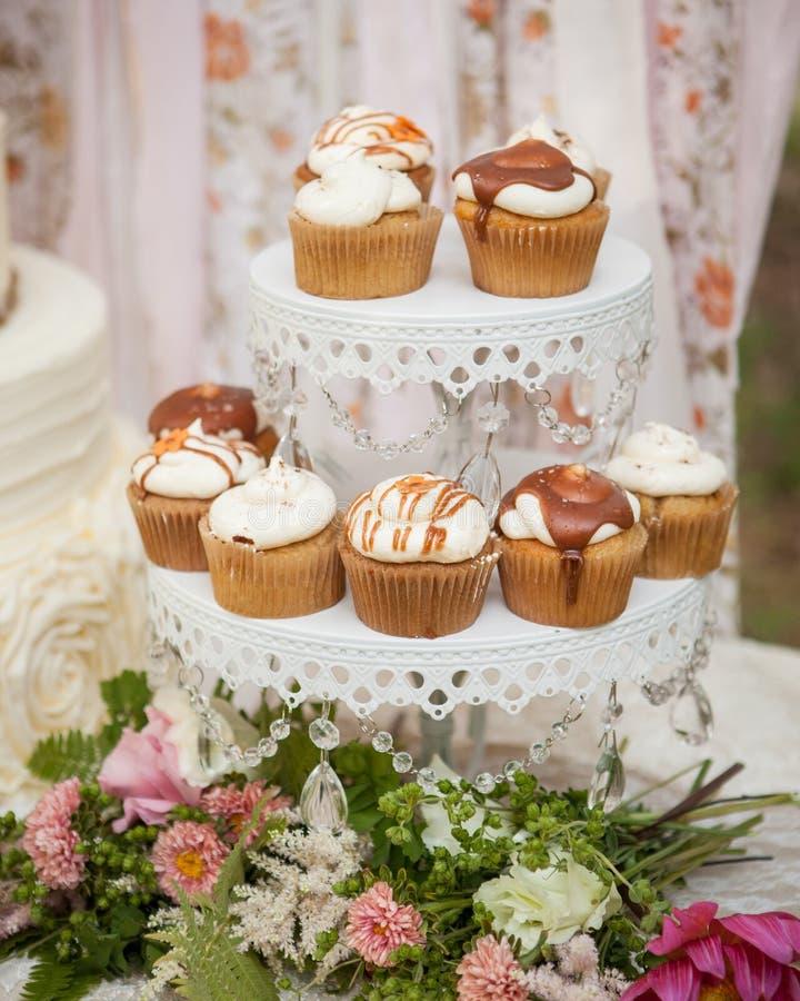 Petits gâteaux de crème et de caramel sur un support blanc avec des fleurs et un contexte de tissu images stock