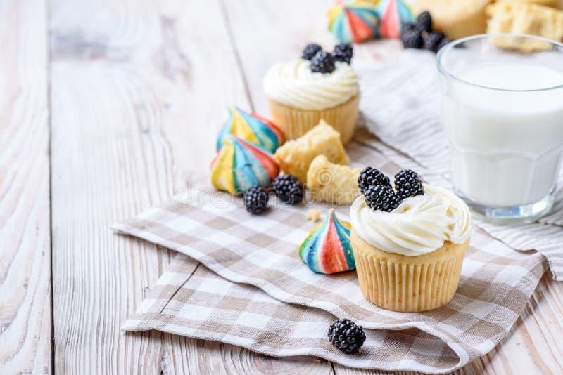 Petits gâteaux de vanille avec des mûres et un verre de lait sur un fond en bois Bise coloré image stock