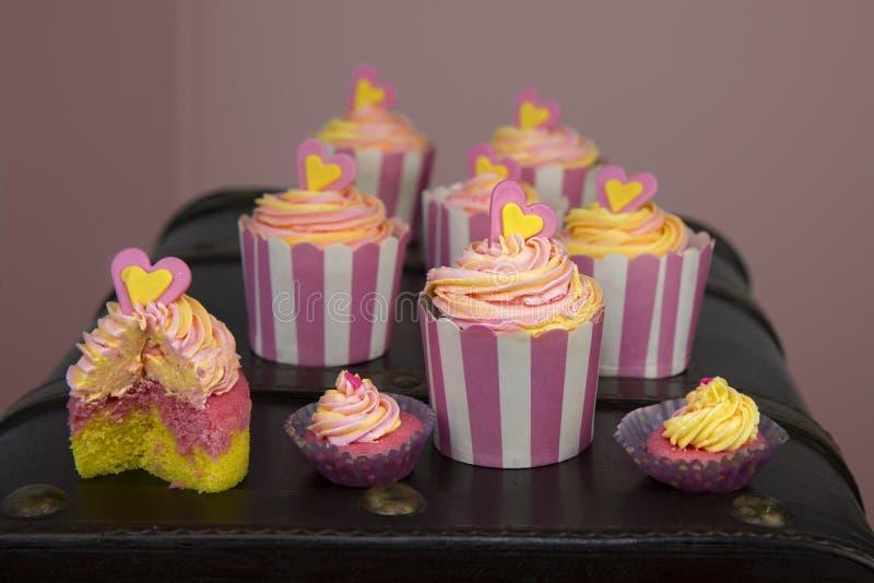 Petits gâteaux roses et jaunes avec un remous du givrage photos libres de droits