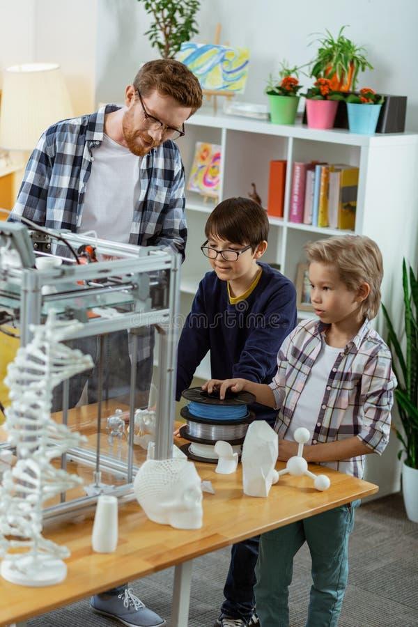 Petits garçons curieux se tenant dans le laboratoire et observant l'appareil photo stock