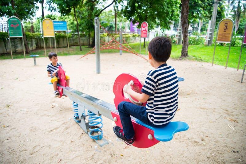Petits garçons jouant la bascule ensemble en parc photos libres de droits