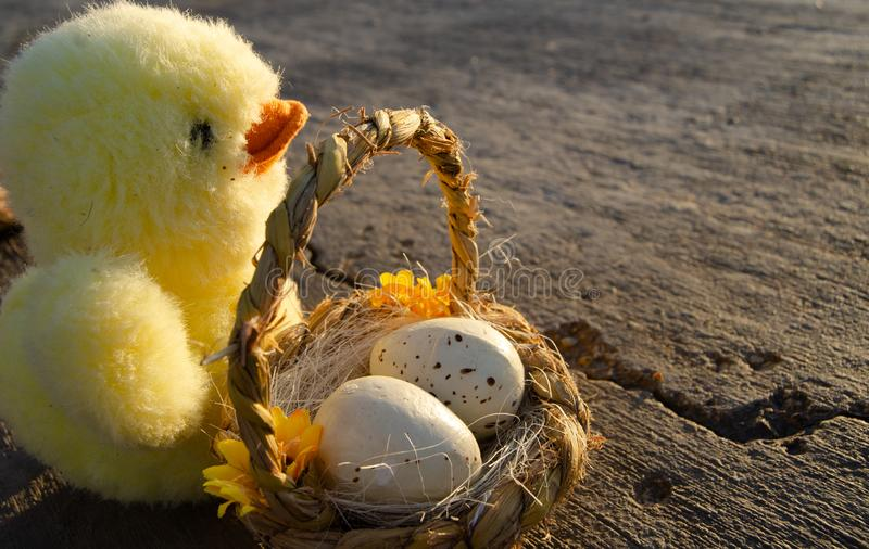 Petits jouet et panier mignons de poulet avec deux oeufs de pâques sur le Doc. de mer - concept de Pâques photographie stock