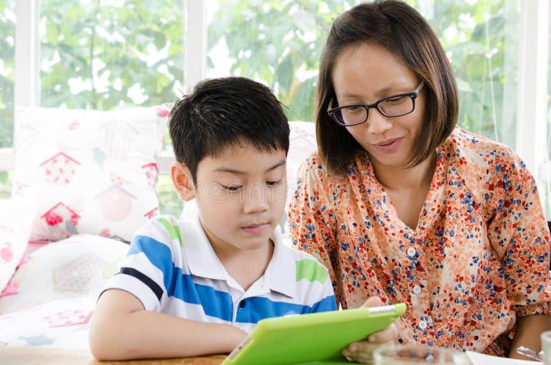 Petits mère et fils asiatiques avec la tablette photo libre de droits