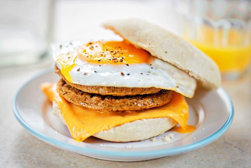 Petits pâtés gratuits de saveur de saucisse de viande sur le fromage et l'oeuf sur le petit pain de petit déjeuner images libres de droits