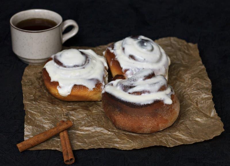 Petits pains avec de la cannelle et le café sur le papier parcheminé et un fond foncé image stock