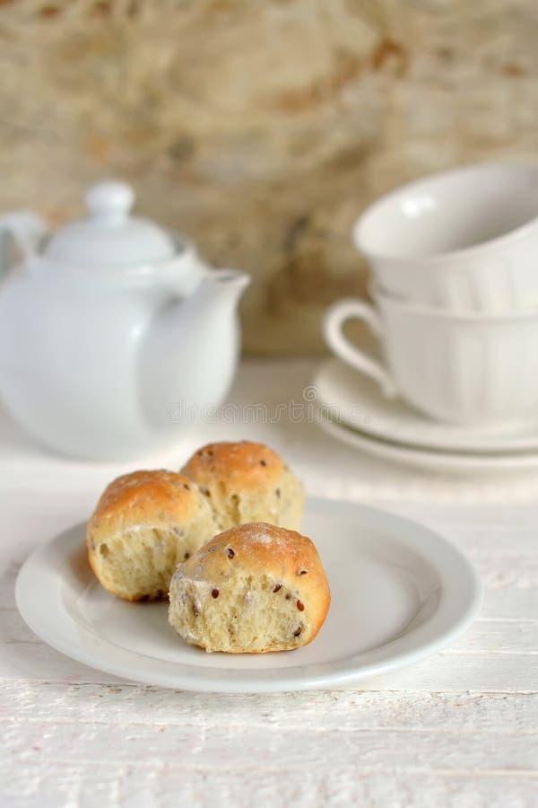 Petits pains avec de la farine de blé entier et des graines de lin d'un plat blanc images libres de droits