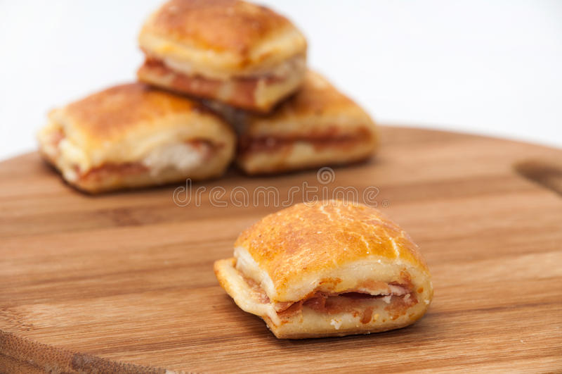 Petits pains avec du jambon et le fromage sur le panneau en bois de cuisine image stock