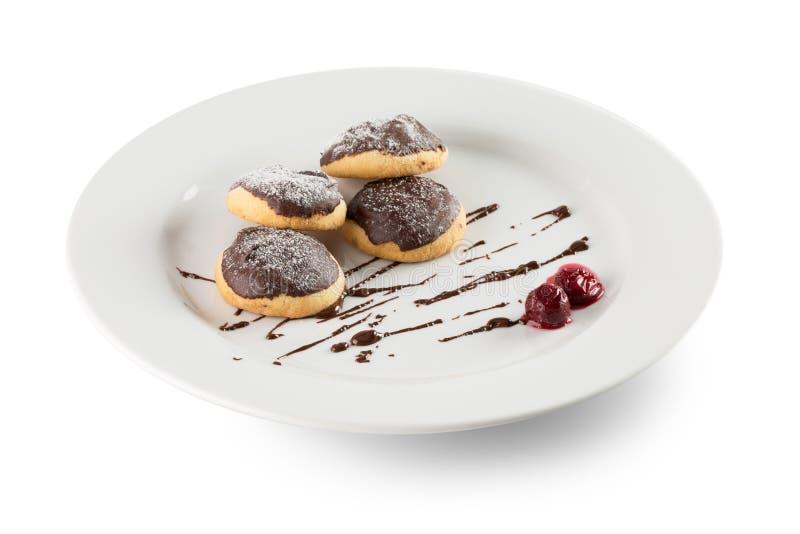 Petits pains avec le glaçage de chocolat du plat blanc d'isolement sur le b blanc images stock