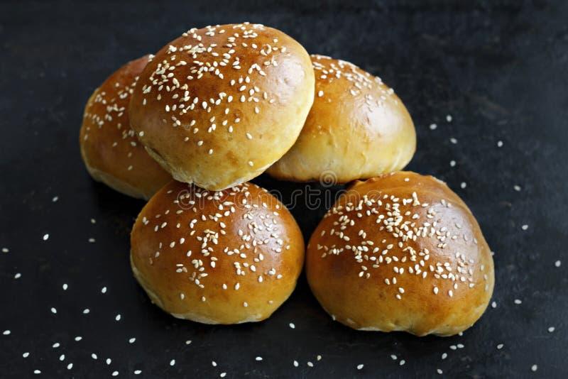 Petits pains avec les graines de sésame sur un fond noir photographie stock