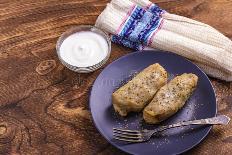 Petits pains chauds de chou avec du riz, viande avec la crème sure dans un plat d'argile Dolmasi de Kelem - feuilles de chou bour photo stock