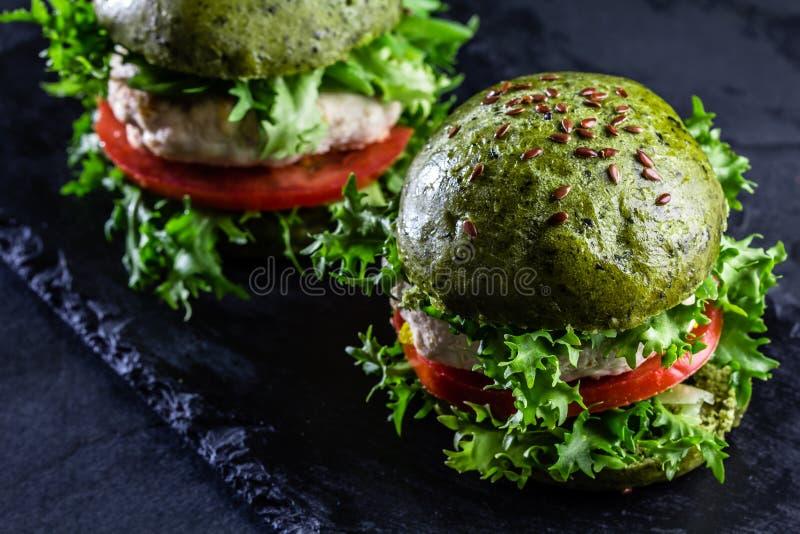 Petits pains d'épinards et hamburgers verts de poulet images libres de droits