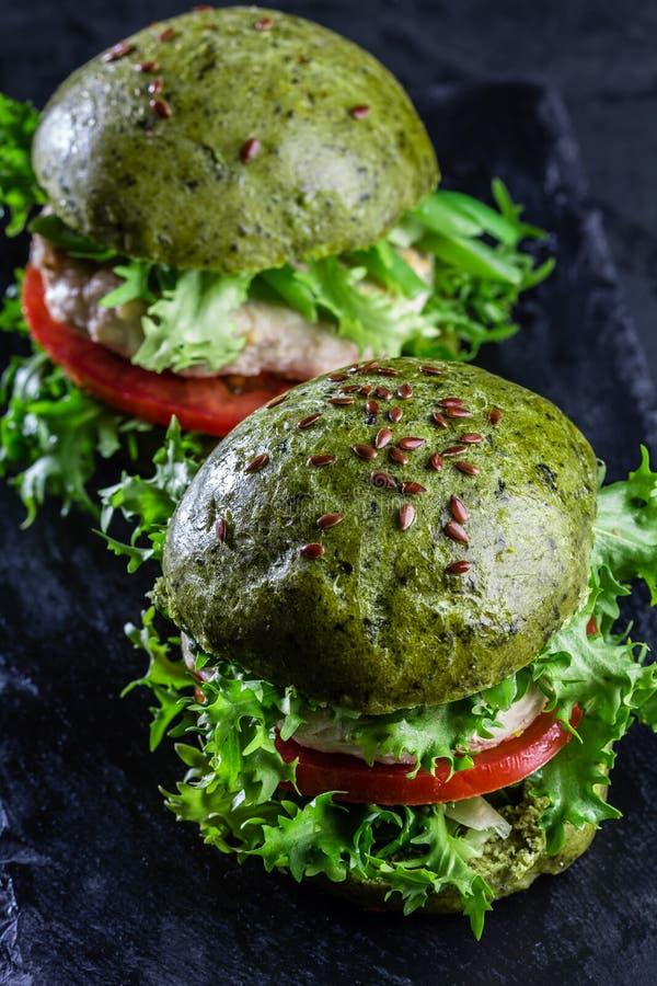 Petits pains d'épinards et hamburgers verts de poulet photos libres de droits