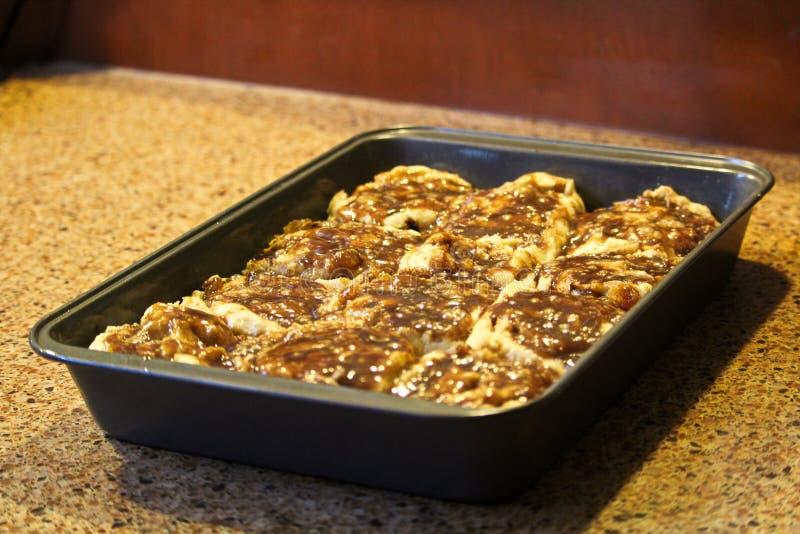 Petits pains de cannelle gratuits de gluten environ à faire cuire au four images stock