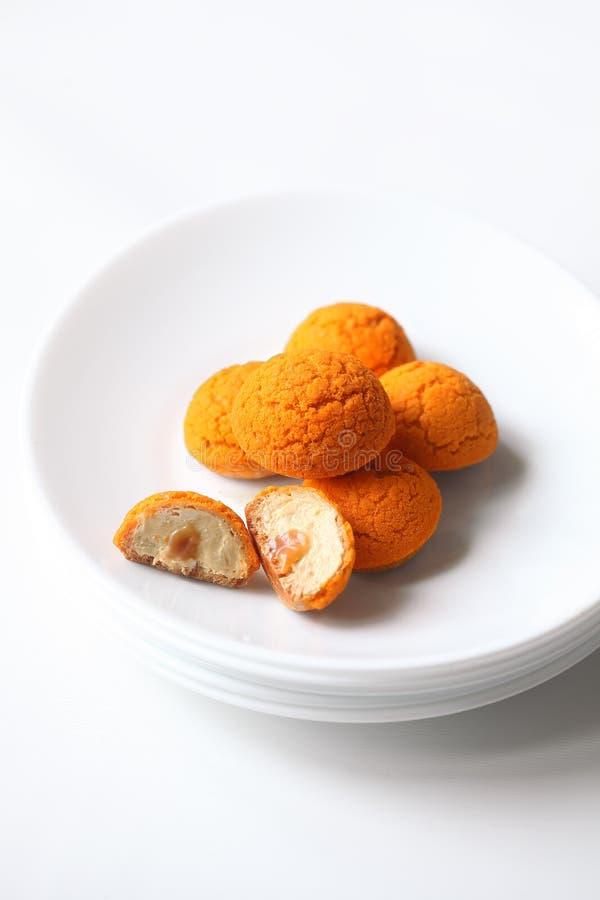 Petits pains de Choux avec les souffles crèmes croustillants de Craquelin remplis de la crème tropicale et de sauce salée à caram photographie stock libre de droits