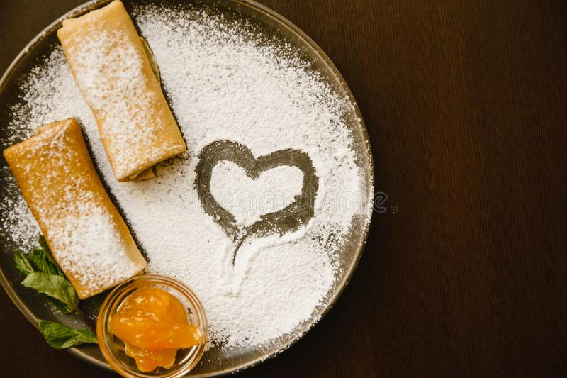 Petits pains de crêpes d'un plat foncé avec du sucre en poudre, la confiture et la menthe Dessert d?licieux photo libre de droits
