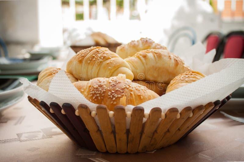 Petits pains de pain fait maison frais avec la graine de sesam dans le panier sur t en bois image stock