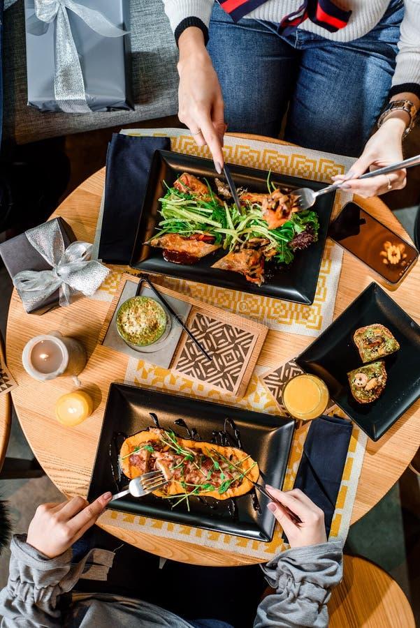 Petits pains de ressort et viande grillée avec la purée de potiron des plats noirs sur une table en bois légère dans un restauran photos stock