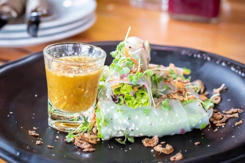 Petits pains de ressort frais thaïlandais végétaux organiques frais avec de la sauce dans le restaurant sur la fin en bois de fon photographie stock