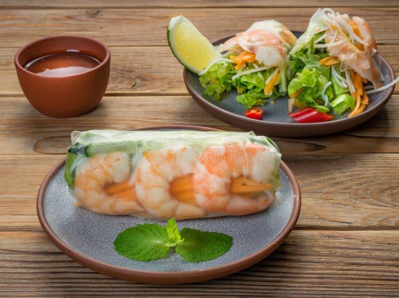 Petits pains de ressort vietnamiens avec des crevettes de deux plats sur le fond en bois Orientation molle photographie stock