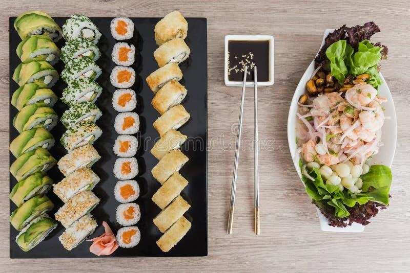 Petits pains de sushi avec le ceviche et la sauce de soja sur une table en bois images libres de droits