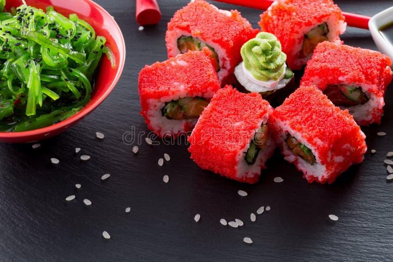 Petits pains de sushi avec le seasalad vert sur une table d'ardoise photo libre de droits