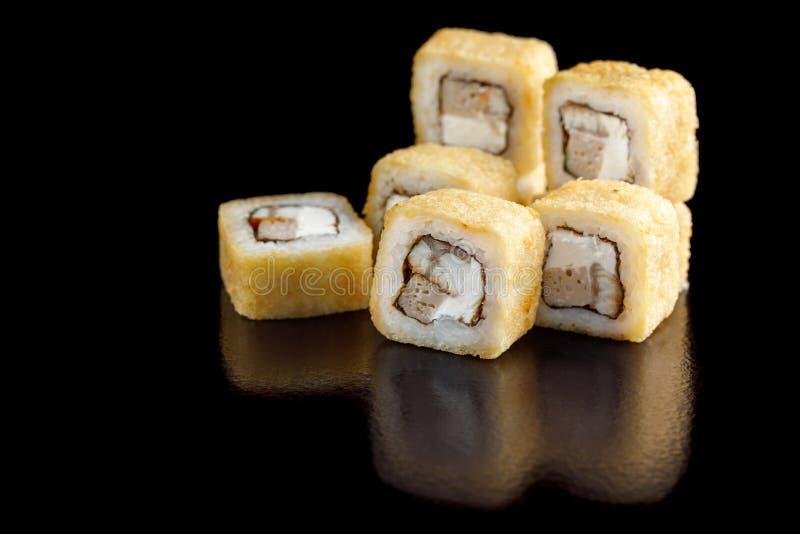 Petits pains de sushi cuits au four avec l'anguille et le poulpe sur un plan rapproché noir de fond photos libres de droits