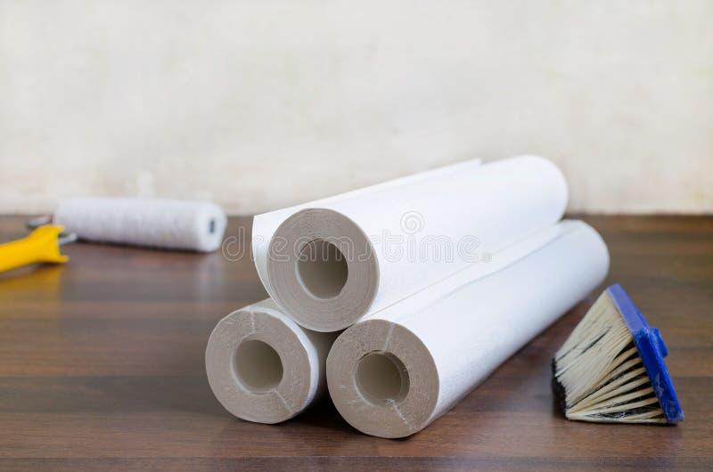 Petits pains et brosse de papier peint sur le plancher pour la réparation à la maison image stock