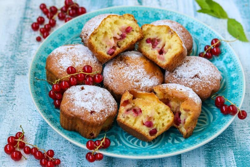 Petits pains faits maison avec des baies, arrosées avec du sucre en poudre, disposé sur une table en bois bleue, style rustique photo stock