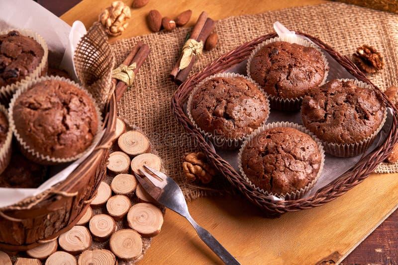 Petits pains faits maison nouvellement fabriqués dans un panier avec des noix et des amandes se trouvant sur une base en bois Vue image stock
